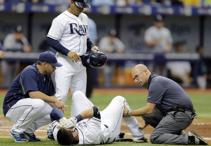Kevin Kiermaier is looked at by a trainer, manager Kevin Cash, and third base coach Charlie Montoyo after getting hit with a pitch from Felix Hernandez during the sixth inning on Wednesday. (Photo credit: AP Photo/Chris O'Meara)