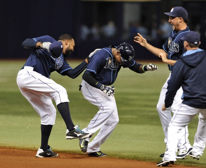 Joey Butler and Matt Andriese celebrate with Tim Beckham after Beckham's two-run walk-off single to beat the Toronto Blue Jays 4-3 on Saturday. Petersburg, Fla. (Photo Credit: AP Photo/Steve Nesius)